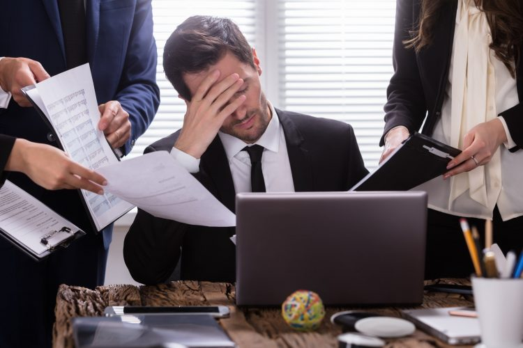 Stressed Businessman Sitting In Office Surrounded By Businesspeople