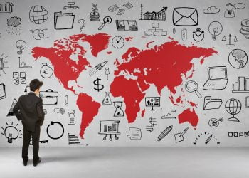 Business Mann vor Weltkarte an Wand mit vielen Icons und Symbolen