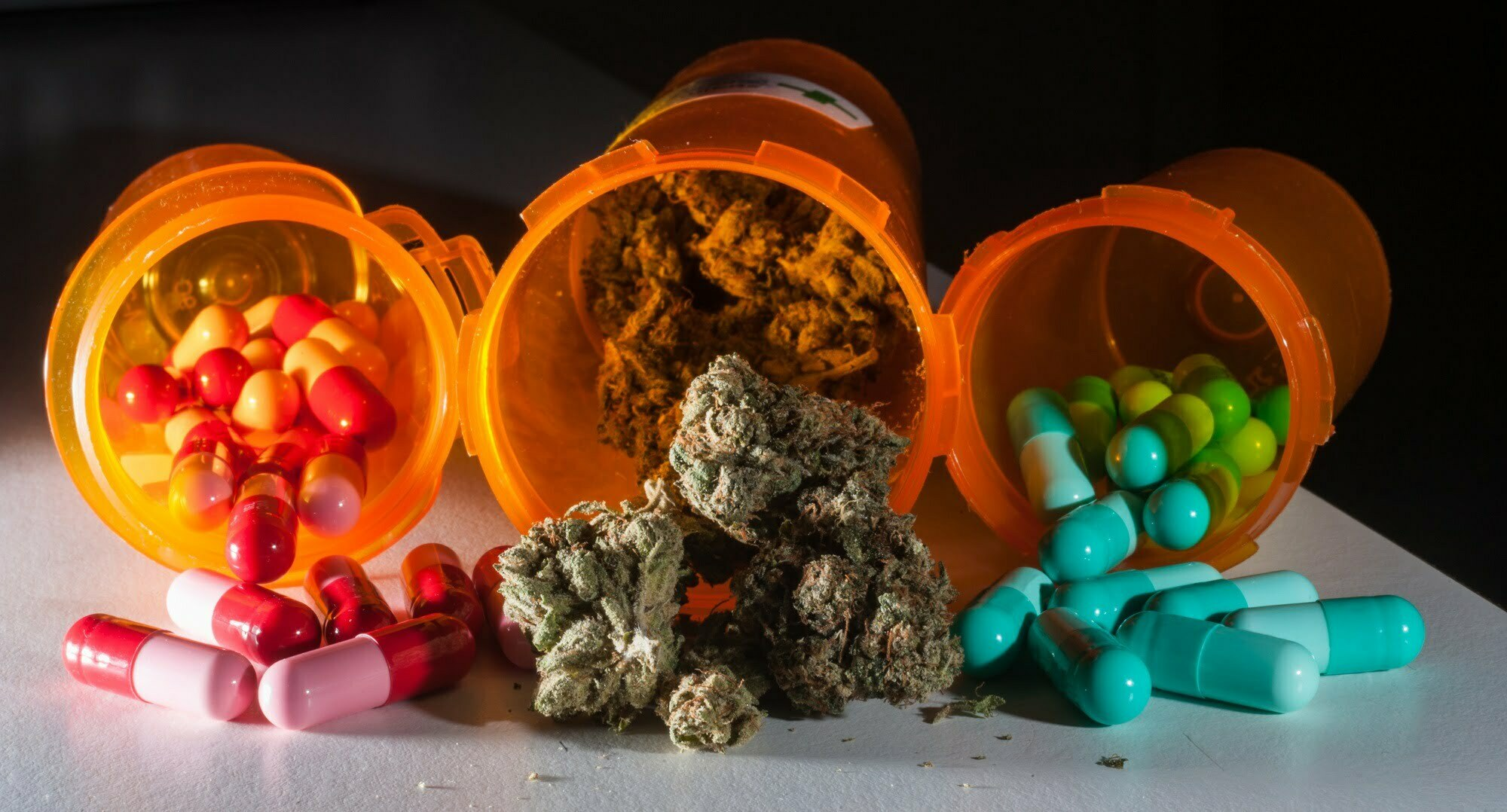 Medical Marijuana and pharmaceutical pills spilled out on a surface