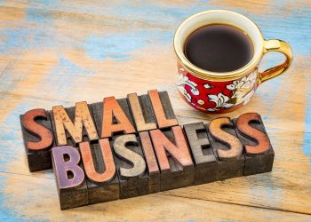 small business - text in vintage letterpress wood type printing blocks with a cup of coffee
