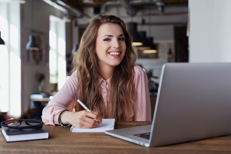 Happy young woman sitting at cafe working remotely