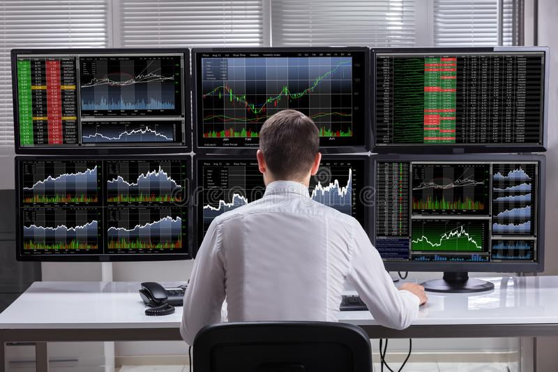 stock-market-broker-analyzing-graphs-computer-screens-side-view-young-male-multiple-126320282