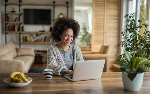 Young happy African American woman using laptop and surfing the net at home.