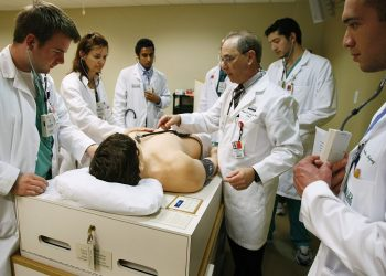 MIAMI - APRIL 02:  James Sikora (L-R), Kay Schmid, Shravan Kandula, Raul Gosthe and Emilio Lopez listen as their professor, Joseph Esterson,  MD, (3rd R) Director, Cardiology Training at The Gordon Center for Research In Medical Education, University of Miami, speaks during a class where they work with Harvey, the cardiopulmonary patient simulator on April 2, 2009 in Miami, Florida. Despite the weak economy there is a need for health care workers, which is reflected in the rise of applications for the University of Miami medical school. Recently a report by Association of American Medical Colleges said the shortage is expected to exceed 124,000 physicians by 2025, and it will be most acute in primary care.  (Photo by Joe Raedle/Getty Images)