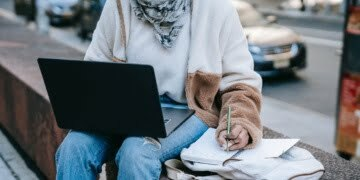 female using laptop and taking notes on street