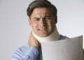 Studio Shot Of Man Wearing Neck Brace Reading Letter