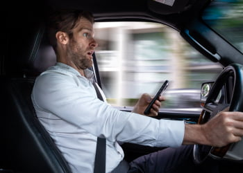 A middle aged caucasian man distracted driving while using a mobile device stops his vehicle suddenly to avoid an accident.