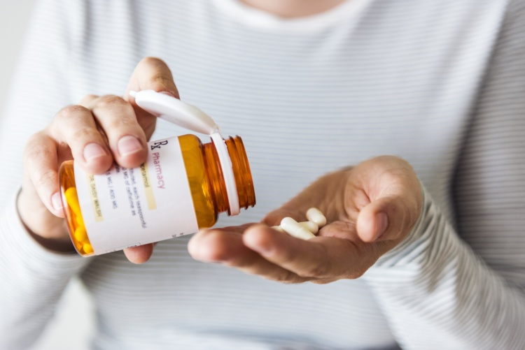 Sick woman taking pills from bottle