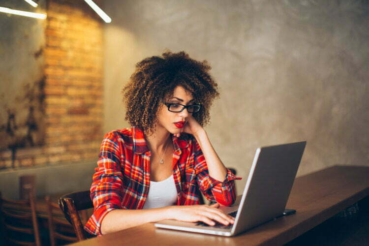 Young woman sitting at cafe working on laptop