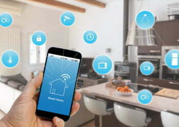 Hand holding smartphone with smart home application on screen
