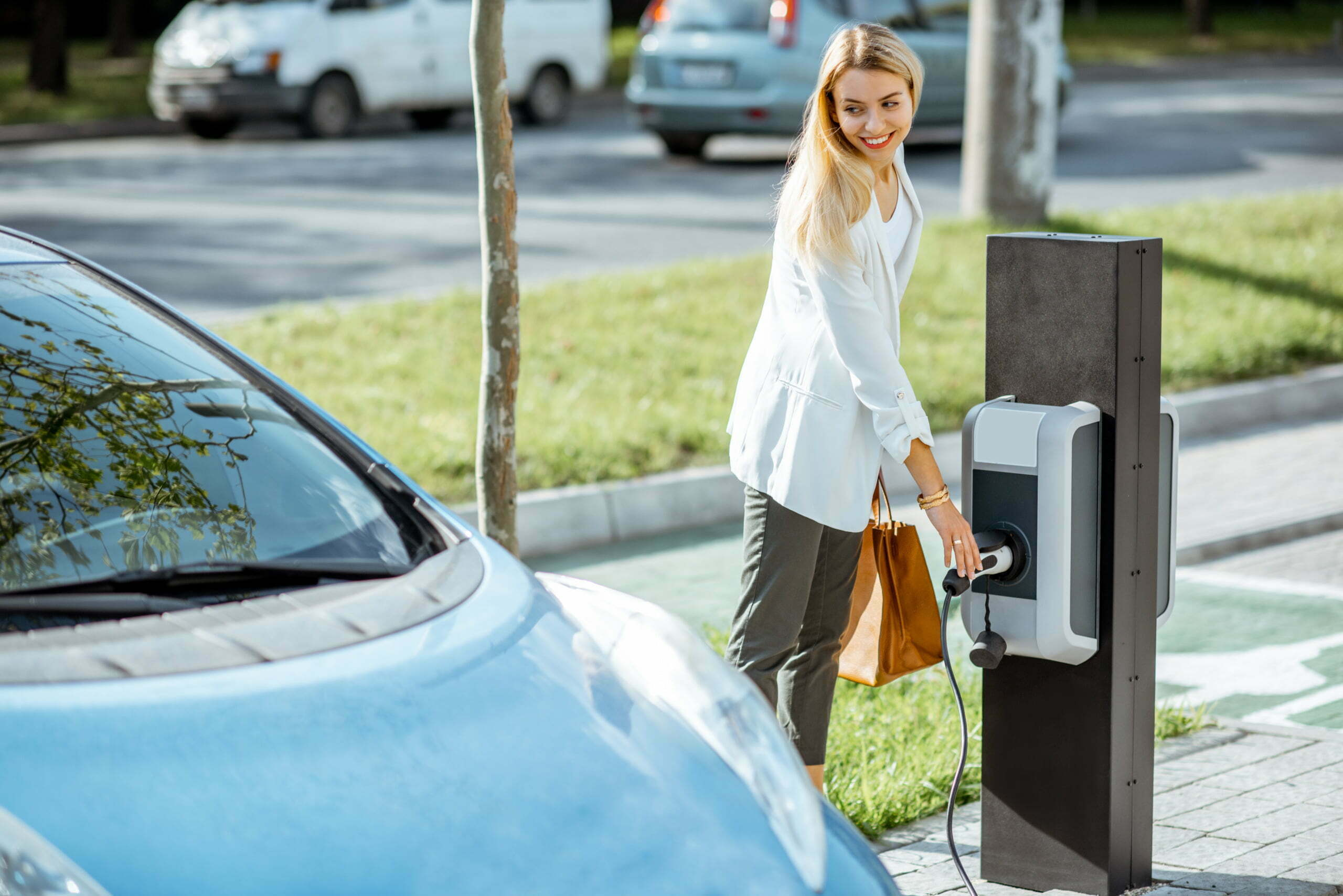 Businesswoman plugging charging gun into the electric station.