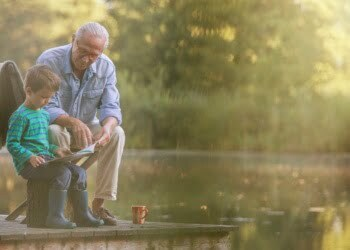 grandfather-and-grandson-reading-at-lake